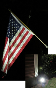 Flag lit by ground staked solar spot light