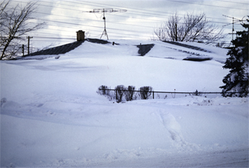 snow drifts covering fence and home